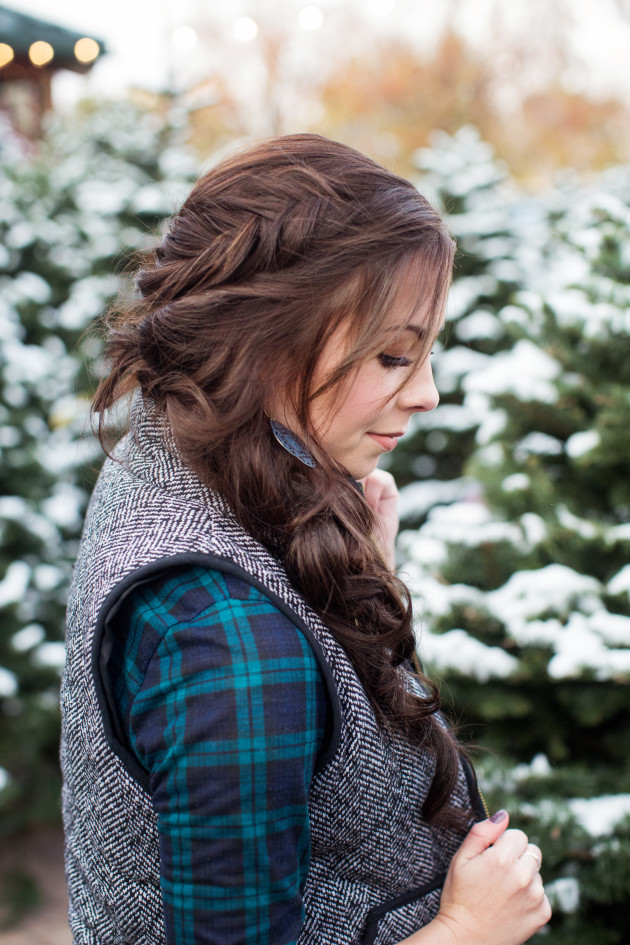 Herringbone vest and plaid with a fishtail crown and knotted messy braid hairstyle