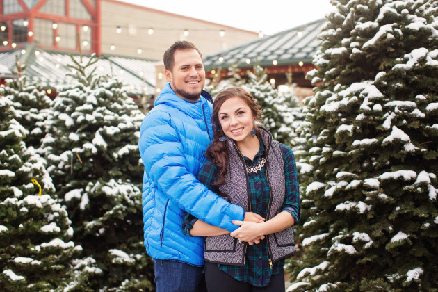 Adorable Couples Christmas Pictures at a snowy Christmas Tree lot with twinkle lights. Wearing herringbone vest and puffer jacket.