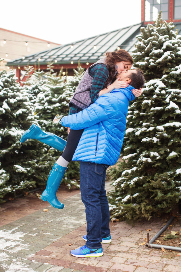 Adorable Couples Christmas Pictures kissing at a snowy Christmas Tree lot with twinkle lights. Wearing herringbone vest and puffer jacket.