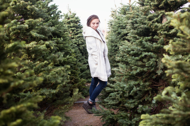 Plaid winter coat winter fashion worn with with jeans and booties and a side fishtail braid in a christmas tree lot.