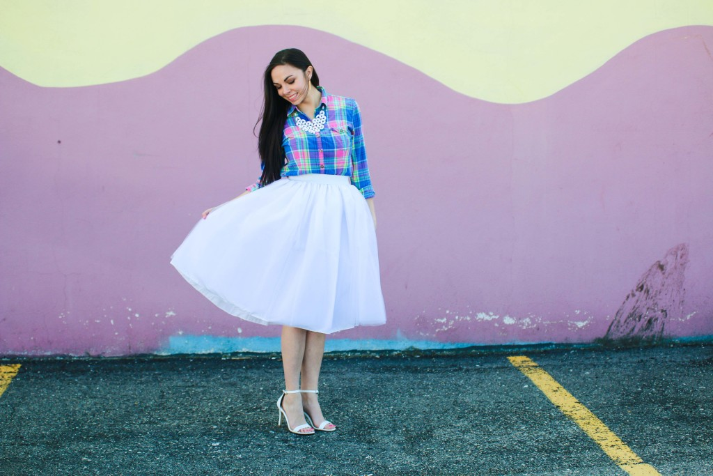 Modest Goddess a modest fashion blogger styles a modest pastel easter outfit featuring a white tulle skirt and a pastel plaid top against a easter colored wall in Salt Lake City, Utah.