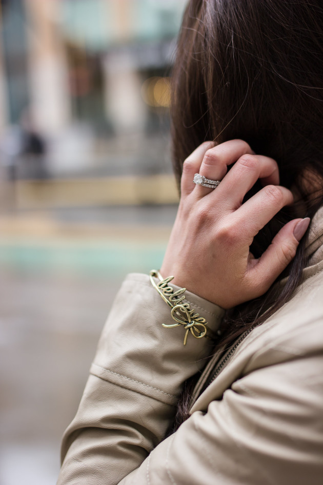 Modest Goddess styles stackable bracelets with a tan leather jacket.