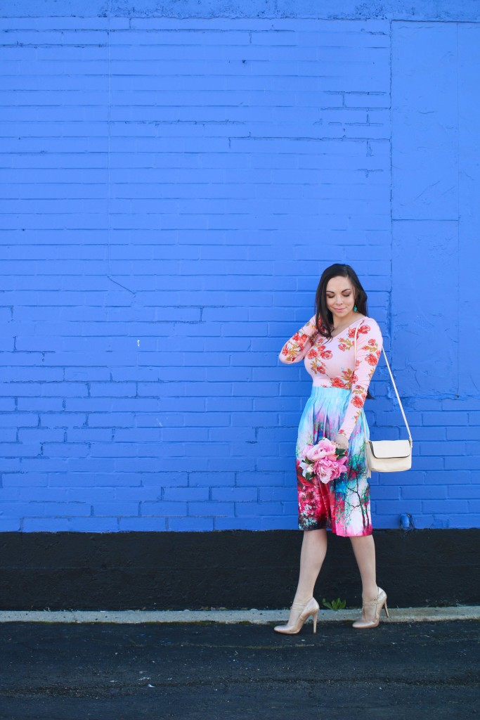 Modest fashion blogger Modest Goddess style a scenic pink and blue watercolor midi skirt with a floral top and a bouquet of peonies for a gorgeous pink and blue modest spring style.