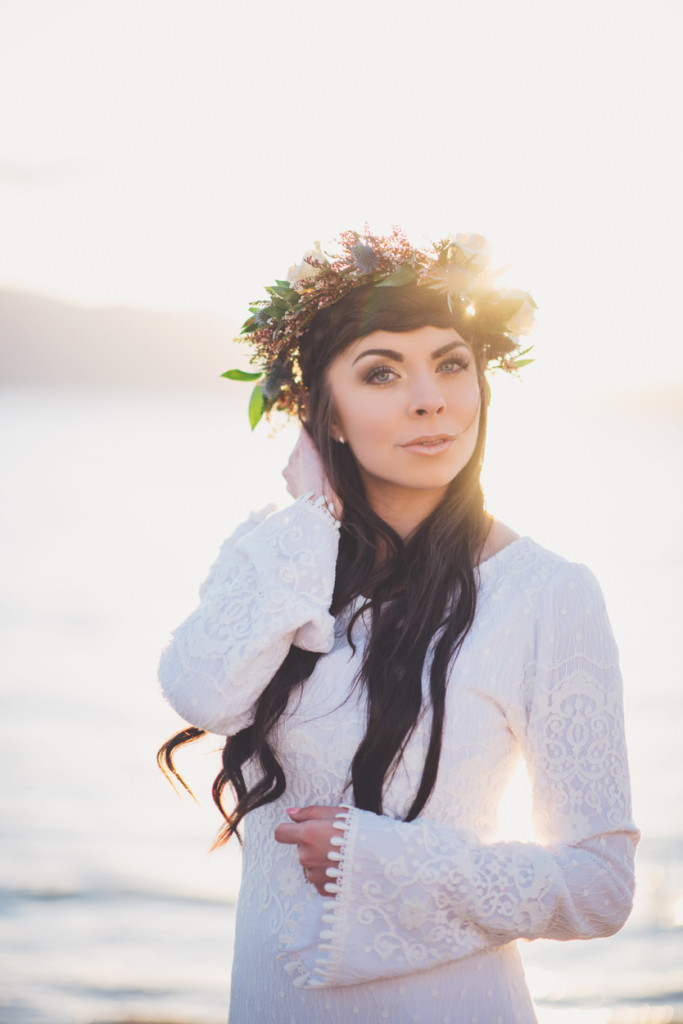 Forehead double braid crown and flower crown bridal hair and bridal flower crown in a long sleeved wedding dress.