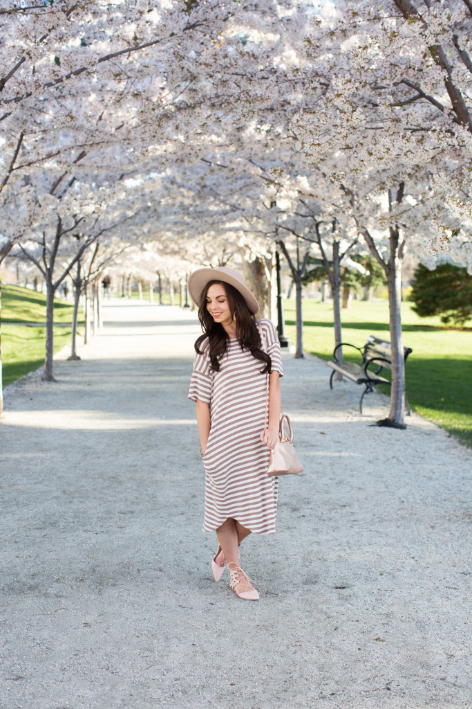 Modest fashion blogger Modest Goddess styles a trendy modest striped swing dress and blush lace-up flats under the canopy of blossoms at the Salt Lake City Capitol.