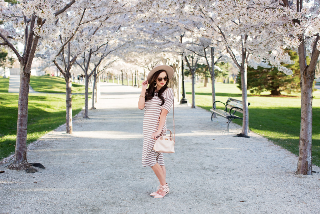 Modest fashion blogger Modest Goddess styles a trendy modest striped swing dress under the canopy of blossoms at the Salt Lake City Capitol.