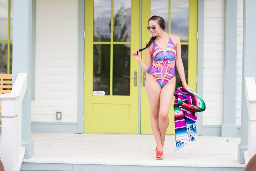 Modest fashion blogger Modest Goddess styles a colorful modest lace-up modest swimsuit from Coral Reef Swim. This colorful modest one-piece swimsuit has a colorful bird print, a lace-up back, and a modest neckline.