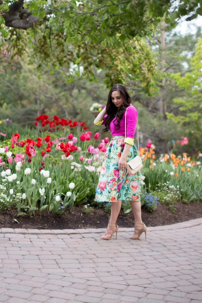 Modest fashion blogger Modest Goddess styles a modest outfit featuring a modest floral midi skirt with a pink sweater layered with a pop of color at the tulip festival.