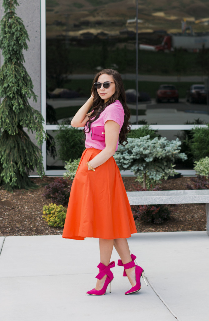 Modest fashion blogger Modest Goddess styles a modest orange midi skirt and a modest embellished pink top from modest online shop She Traveled with hot pink bow heels for a cute modest pink and orange outfit.