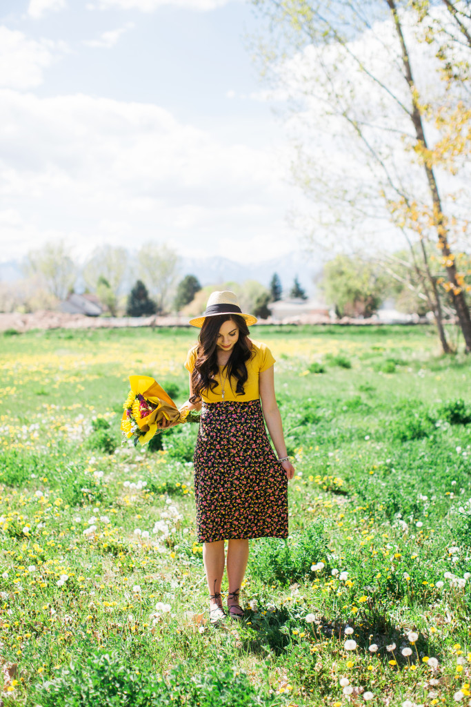 Modest fashion blogger Modest Goddess styles a yellow and black floral modest summer dress with sunflowers and lace-up flats for summer.