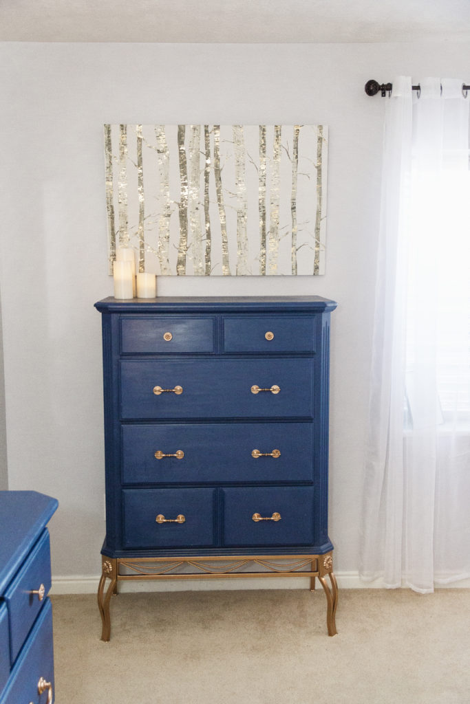 Blogger Modest Goddess redecorates her master bedroom for a navy and copper master bedroom DIY home decor makeover including a DIY upholstered headboard, thrifted furniture, DIY chalkpainted furniture, and DIY spray painted decor!