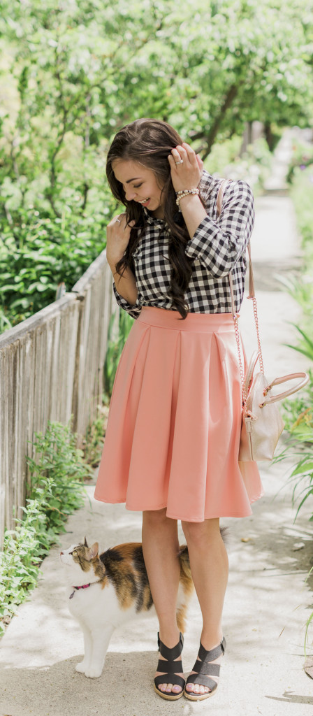Modest fashion blogger Modest Goddess styles a modest coral midi skirt from Sexy Modest boutique with a black and white gingham top and black wedges for a cute modest summer skirt outfit.