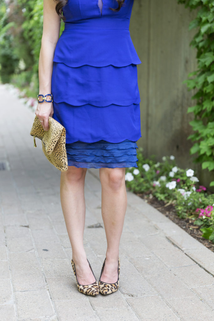 Modest fashion blogger Modest Goddess styles a modesty hack of a short scalloped blue dress with a slip extender and a nude layering tee accented with pops of leopard.