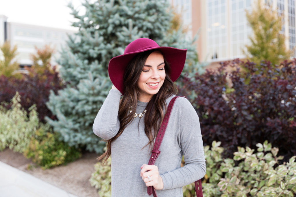Modest Fashion Blogger Modest Goddess styles a modest fall outfit featuring a grey swing dress and pops of burgundy with this burgundy floppy hat and burgundy suede saddle bag.