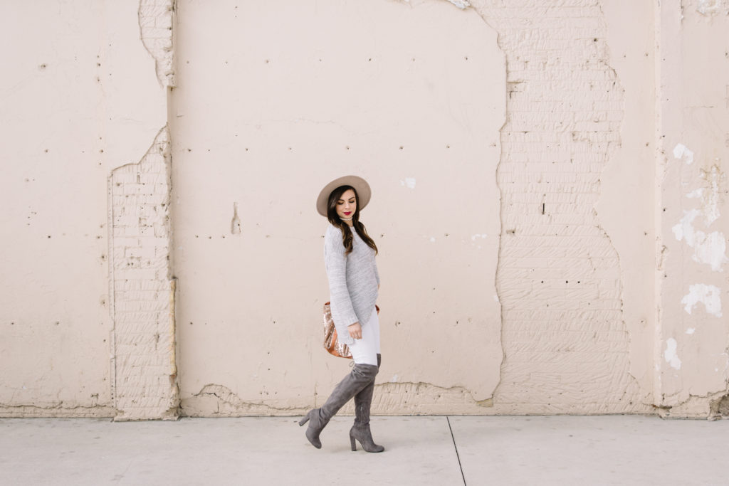 Modest fashion blogger Modest Goddess styles modest over-the-knee suede boot style with white jeans and a sweater.