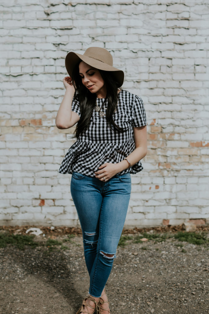 Modest fashion blogger Modest Goddess styles a gingham peplum top, distressed jeans, and a hat.