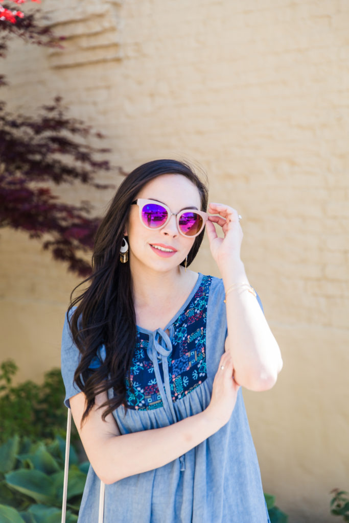 Modest fashion influencer Modest Goddess styles a modest chambray outfit with purple sunglasses.